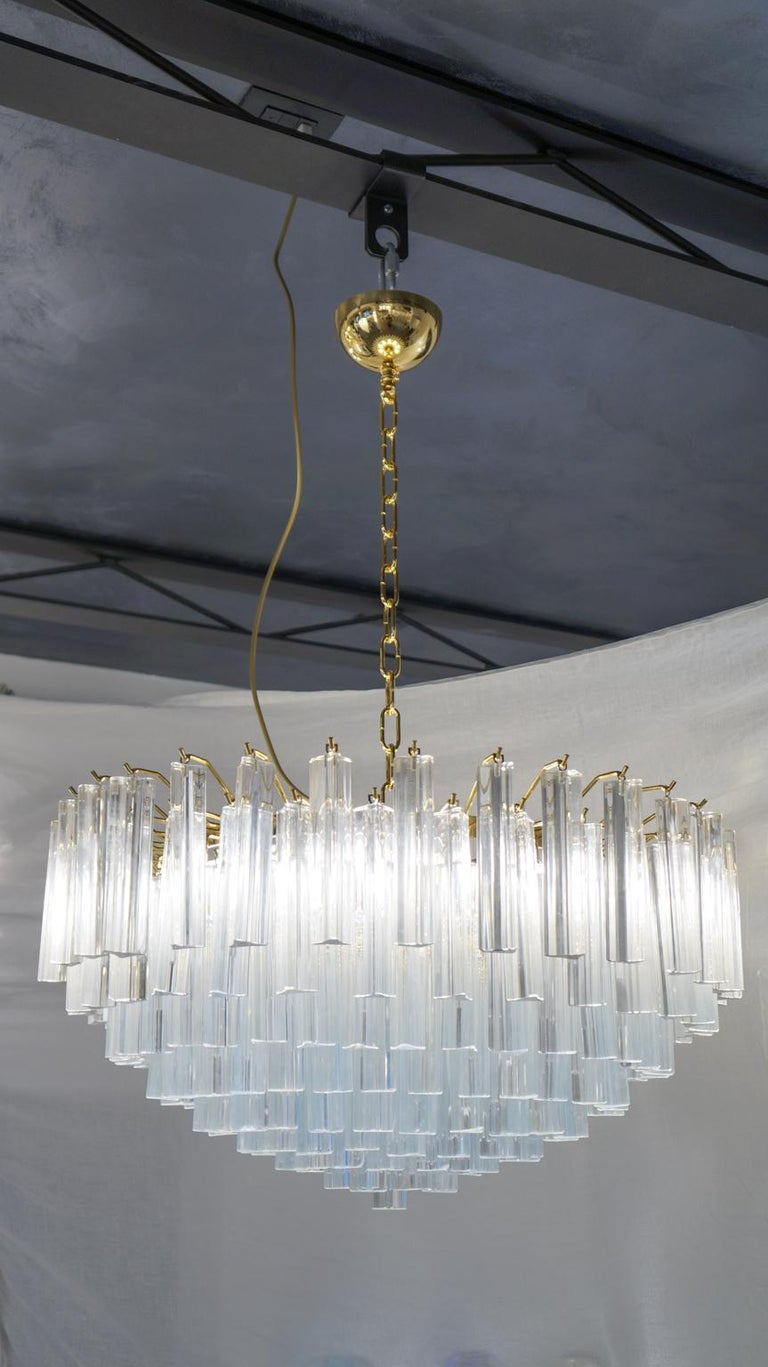 Murano blown glass chandelier with 169 elements in antique crystal, gold finish structure and 9 lights E26 / E27. The elements of this typical chandelier are called Triedri, for its triangular shape. The assistants take a small quantity of glass