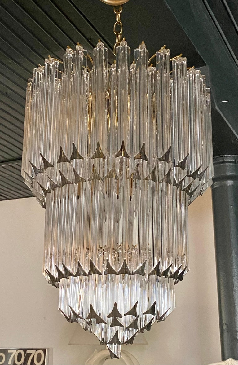 Large and Grand round Mid-Century Modern glass and brass seven-tier waterfall chandelier in the style of Venini Camer, Italy. This impressive sculptural wedding cake chandelier is constructed of 125 clear solid crystal glass prisms. Would be great