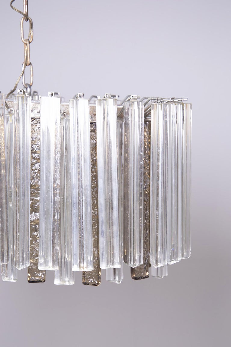Beautiful chandelier made by Venini, steel structure and Murano glass stem in 1950. The heavy chandelier is composed of small white and ivory Murano glass staves, respectively triangular-shaped white ones and rectangular-shaped ivory ones, also the