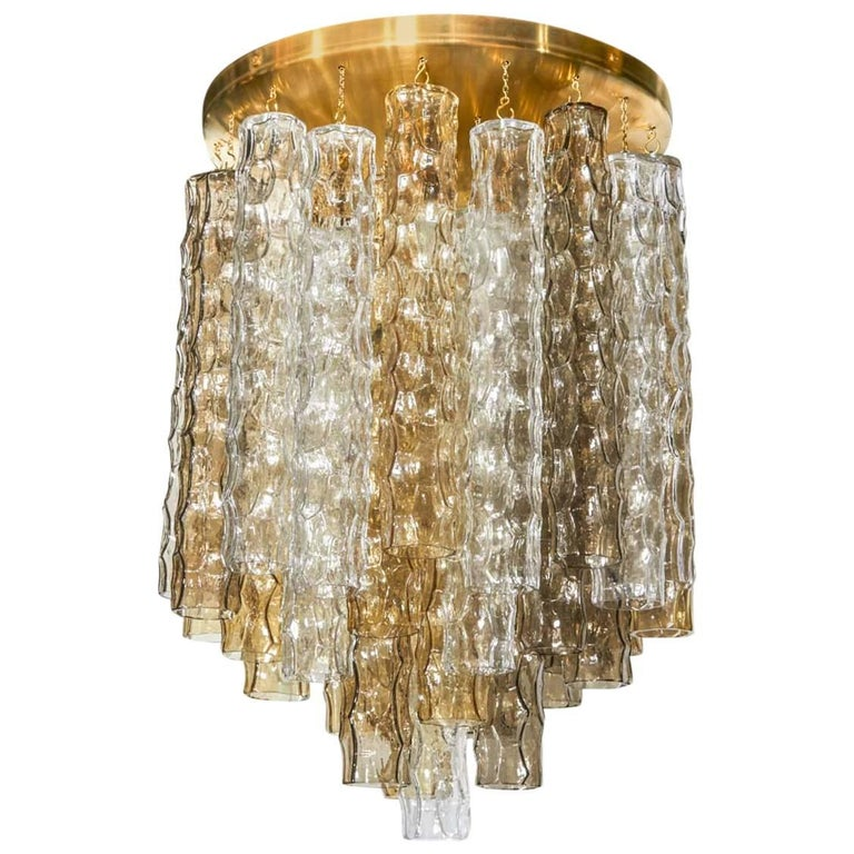 Mid-Century Modern Hollywood Regency chandelier comprised of three tiers of hand blown Murano glass pendants with bamboo texture and design. The glass pendants come in alternating colors (smoked grey, amber, and clear). Features a large brass dome
