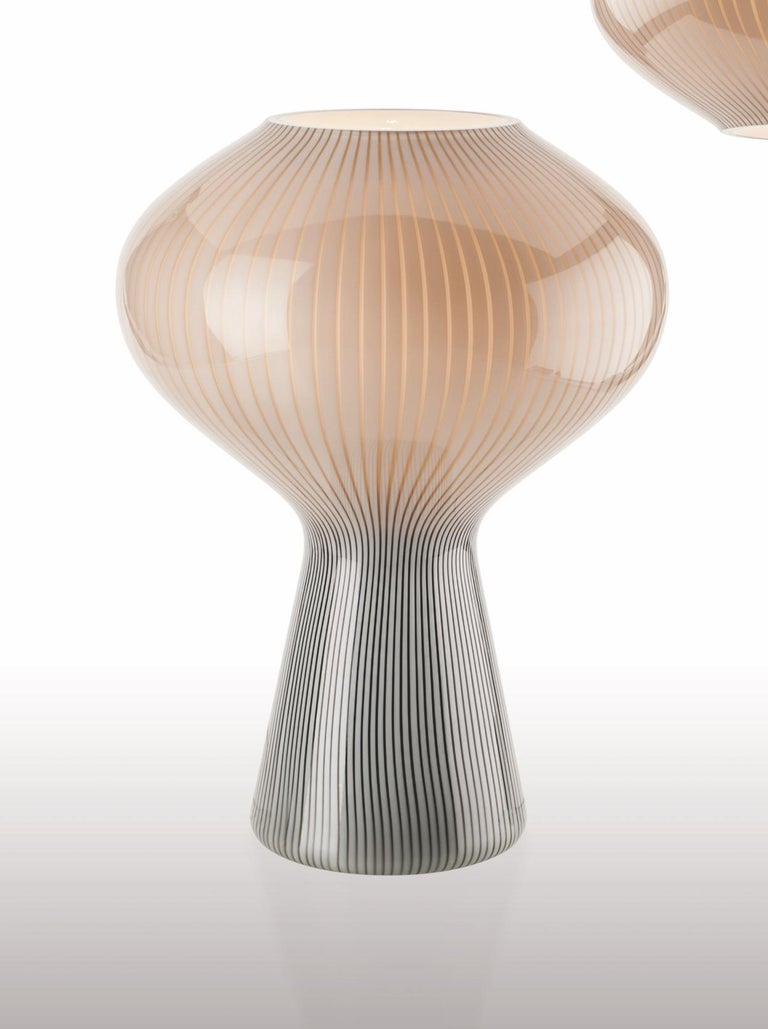 Glass table lamp with an interesting shape and two-tone coloring. Its sleek design and muted color pallette make it a modern, simple and understated lighting option for any space. Also available as a pendant light. 