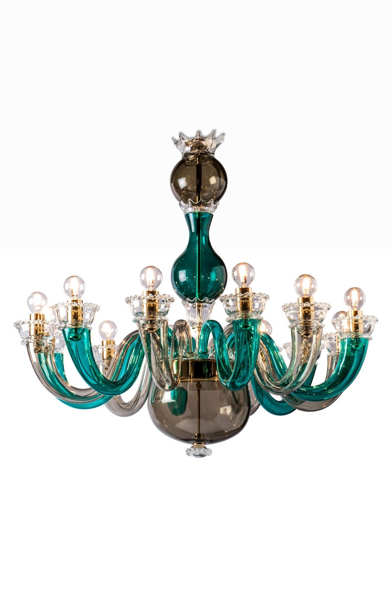 Glass chandelier with gold plated metal finishes and chain. A colorful chandelier with a touch of elegance that adds color to any living room or entrance space. Also available in various sizes and colors.   Light source: 12 x max 60 W E 14.