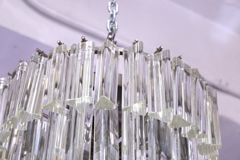 Italian modern glass prism chandelier by Venini, made of multiple tiers of triedri glass prisms. The piece is in great vintage condition with age-appropriate wear. Also available as a pair.