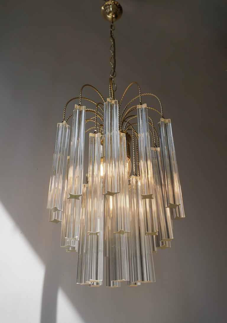 Beautiful Venini multi-tier four-light chandelier featuring four point (Quatro Punta) angle cut-crystal and brass-plated steel frame. Uses four E14 - 40 watt candelabra size bulbs.