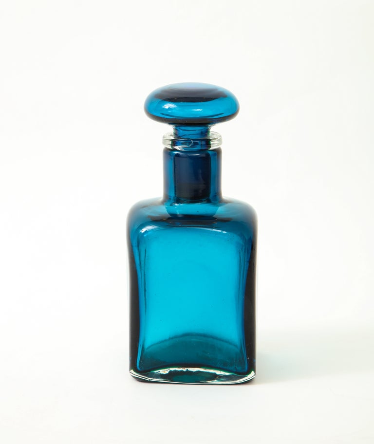 Large bottle with square base in oceano (ocean) blue composite glass with several layers of color and stopper, Italy, 1950s.  Literature: Marino Barovier, Carla Sonego, Paolo Venini e la sua fornace, Skira, Milano, 2016,  p. 275.