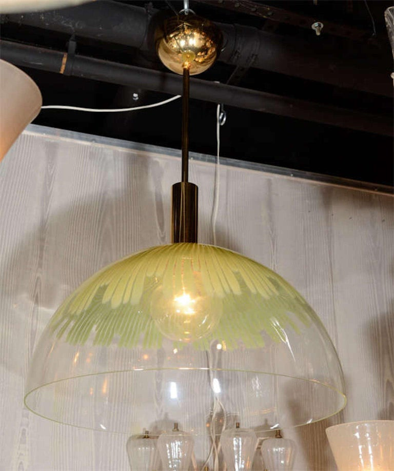 A documented pendant light by designed Ludovico Diaz de Santillana. Santillana was the director and a designer for the famed glass house Venini from 1959-1985. Dome shade is hand blown clear glass with green stripes suspended from a gold plate on