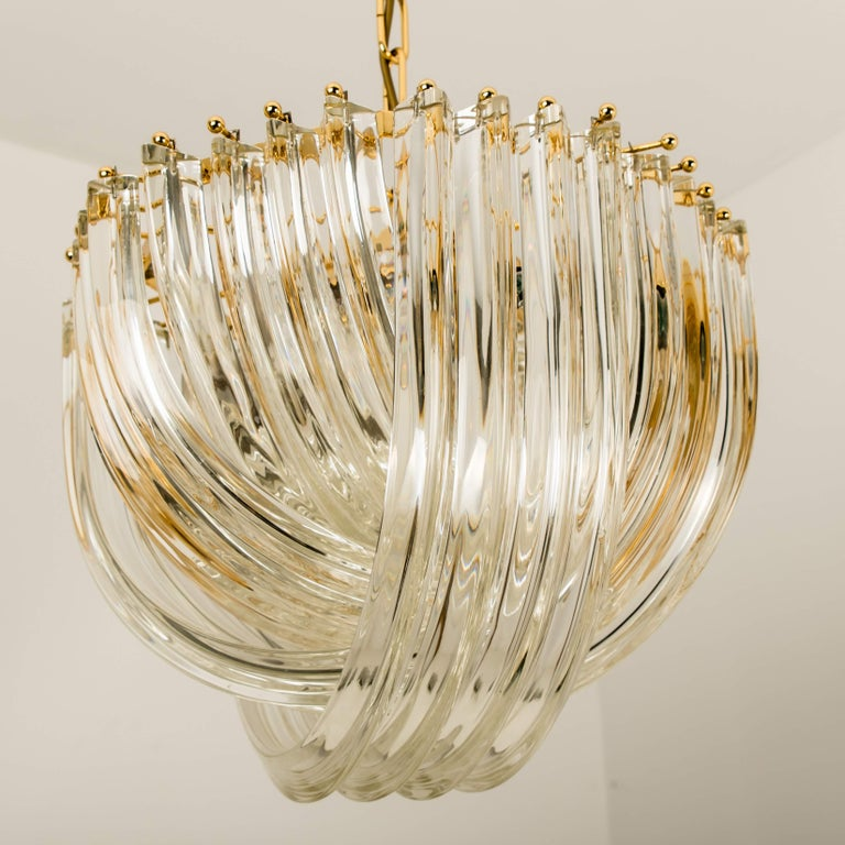 One impressive light fixture by Venini, Italy. Manufactured in circa 1970 (late 1960s and early 1970s). A handmade and high quality piece. Large curved crystal Murano glasses in different length mounted on a gold-plated brass frame. The crystals are