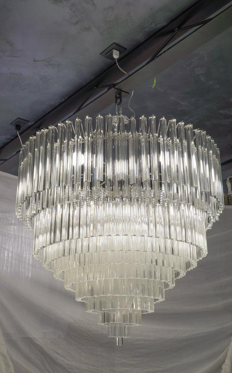Murano glass chandelier with 457 elements in crystal, nickel finish structure and 12 E26 / E27 bulbs. The elements of this typical chandelier are called Triedri, for its triangular shape. The assistants take a small quantity of glass from the oven.