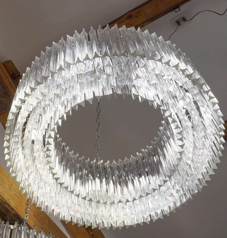 Murano glass chandelier with 370 elements in crystal, nickel finish structure and nine E26 / E27 bulbs. The elements of this typical chandelier are called Triedri, for its triangular shape. The assistants take a small quantity of glass from the