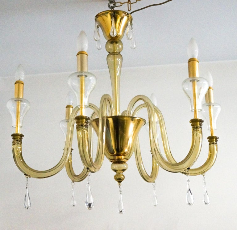 Elegant Venetian glass chandelier with six lights color smoked and crystal. This fantastic chandelier with a golden finish. Attributed to Venini and executed in the circa 1970s.  The Murano glass chandelier is nothing like a typical fixture made
