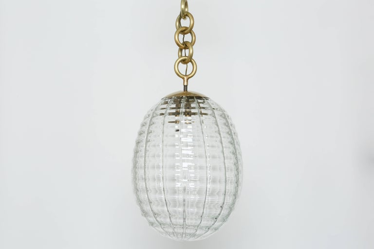 Venini ceiling pendant. Made with hand blown glass and brass. Italy, 1950s. Two pendants available.