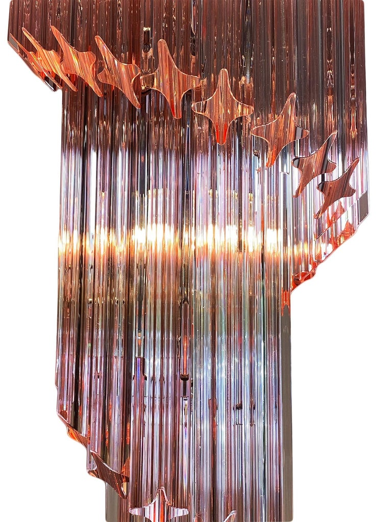 """Pink Murano glass Venini """"triedri"""" spiral chandelier. This piece by Venini is in the iconic """"spirale triedri"""" shape and features beautiful hand-blown glass components in a pink hue. They glass is layered in a downward spiral on a chromed structure."""