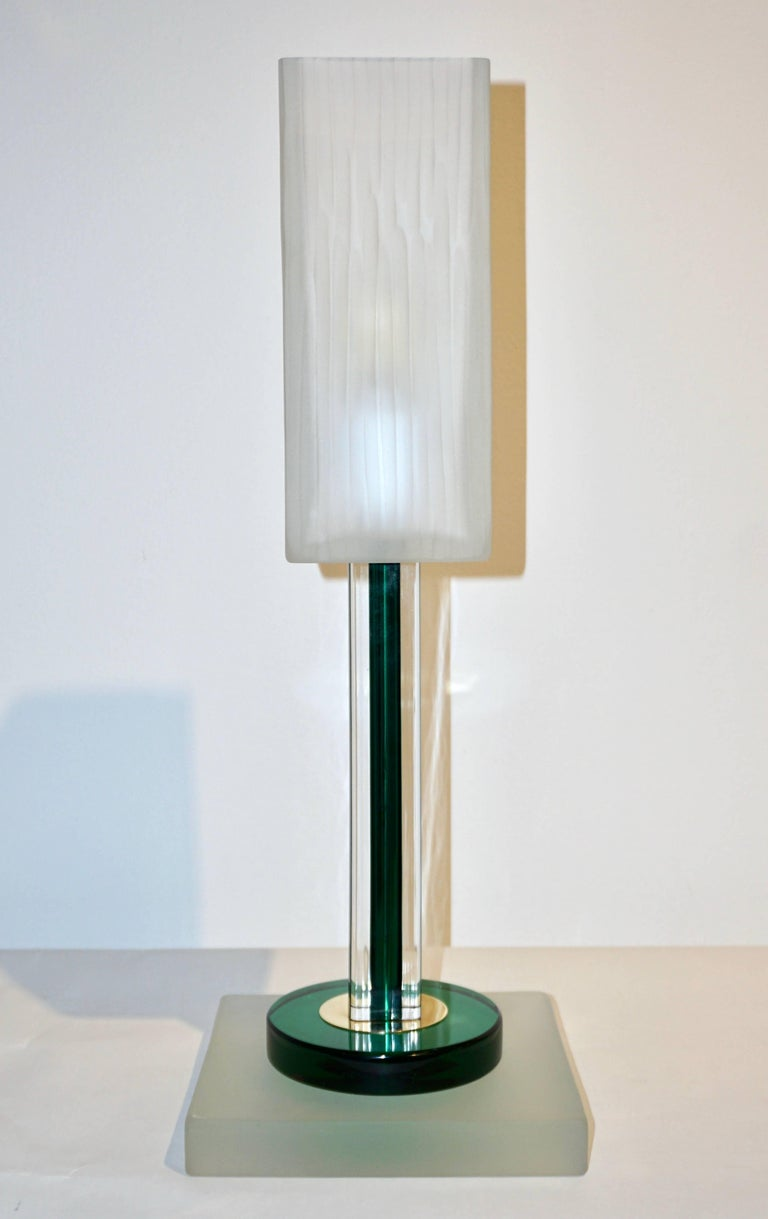 A rare Italian Minimalist pair of lamps signed Venini 1992 of modern geometric design, the square shaped central support presents a green Murano glass core worked ad incalmo overlaid in crystal clear glass, raised on a stepped base with a green