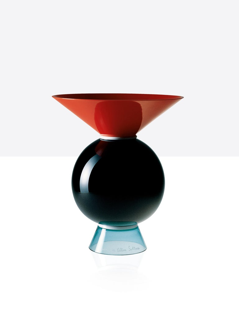 Venini glass vase with geometric, circular shaped body and triangular neck and base. Designed by Ettore Sottsass in 1994. Featured in coral red, milk-white, black and light green colored glass. Perfect for indoor home decor as container or strong