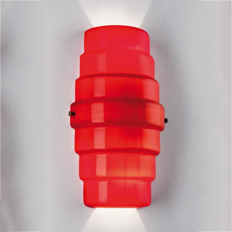 Zoe wall sconce in red glass. Its shape is reminiscent of a lantern and brightens any living space with its bold red color.   Light source: Halogen 1 max- 70 W E27. Dimensions: 20 cm D x 20 cm W x 36 cm H.