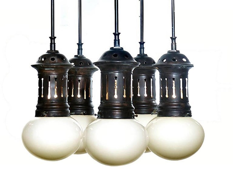Stroll into New York's Park Avenue armory and you will see the striking multi-globe lamps in the front lobby. This amazing chandelier has that early municipal look. These early and elegant bun shaped hand blown shades are Vaseline over white