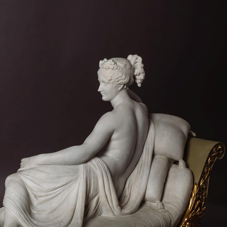An exceptional Italian Grand Tour model of Pauline Bonaparte Borghese as 'Venus Victrix' after Antonio Canova. The nude figure reclining on a grey painted and gilt neoclassical récamier holding an apple in her hand.   This iconic marble figure is