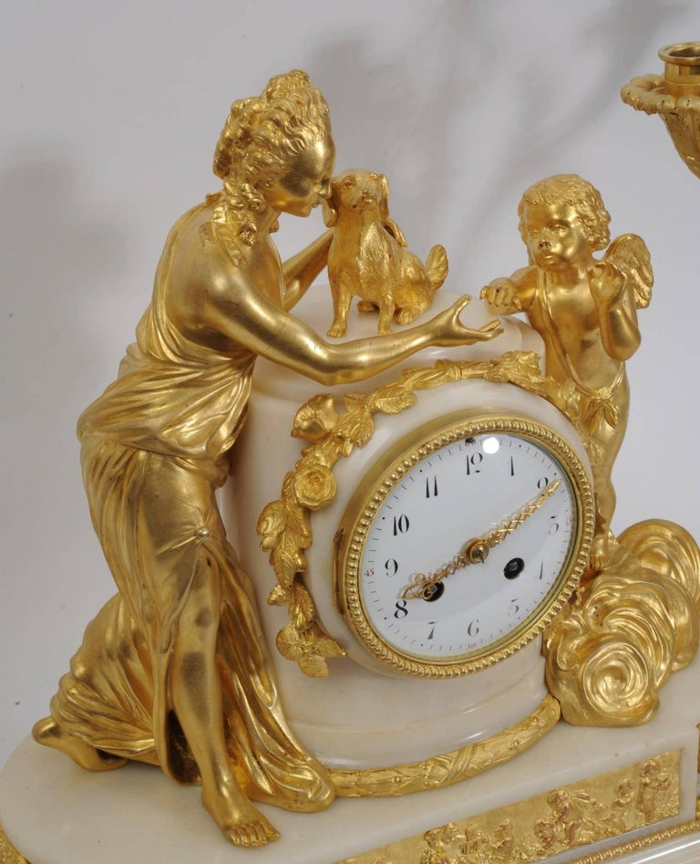 A large and exceptional original antique French ormolu and marble Louis XVI style clock set. The beautiful young Venus stands with a small dog, a symbol of fidelity. Amour is represented in the heavens by a putto standing amongst the gilded clouds.
