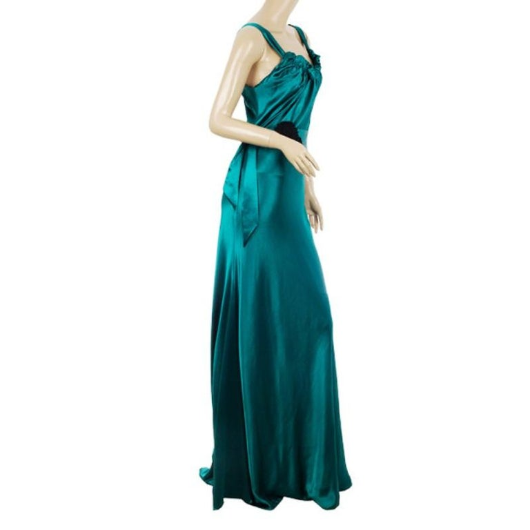 This breath taking teal evening gown by Vera Wang is made from an acetate blend with an asymmetrical flowing hem. It comes with a waist belt accented with floral detailing and is gathered at the top.  Includes: The Luxury Closet Packaging  The