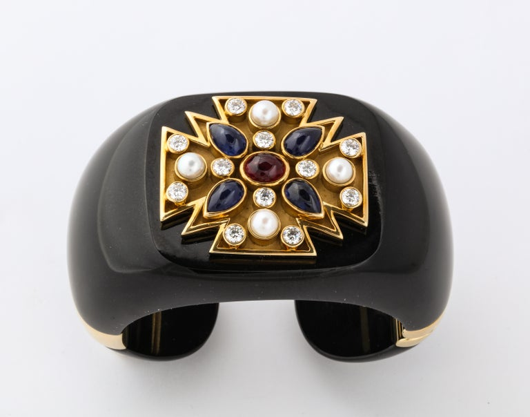 Originally designed for Coco Chanel in the 1930's, the maltese cross cuff remains one of Verdura's most truly iconic designs.  The bold cuff is carved from black jade and the maltese cross is set with pearls, diamonds, sapphires and a central ruby.