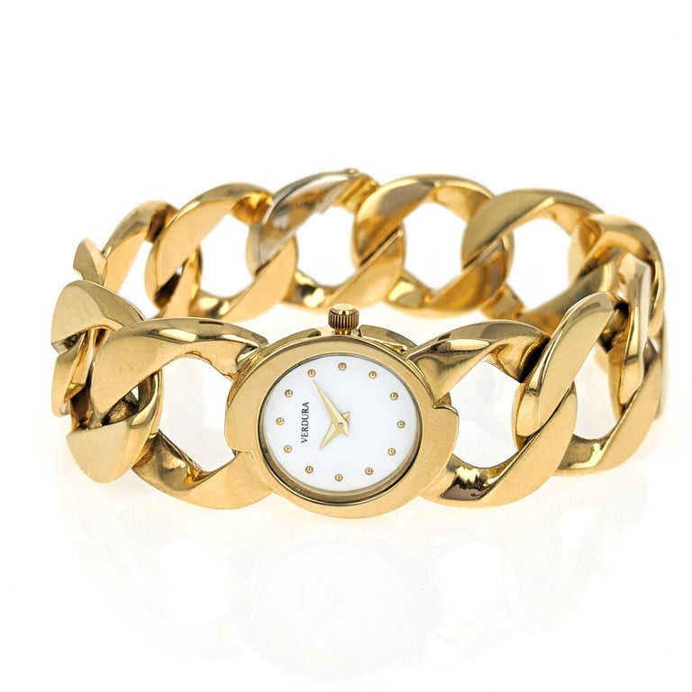 This 18 karat yellow gold watch features Verdura's classic curb link bracelet with a round white lacquer dial and gold dot hour markers. The back of the case is inscribed