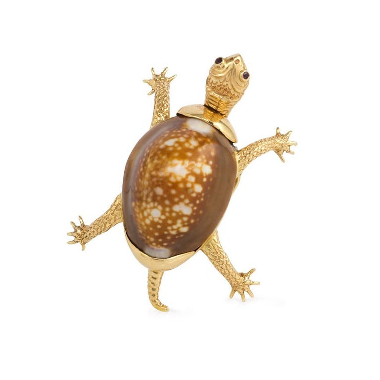 A mid-century engraved gold and cowrie shell brooch in the form of a turtle with ruby eyes, in 14k. Verdura  In superb condition