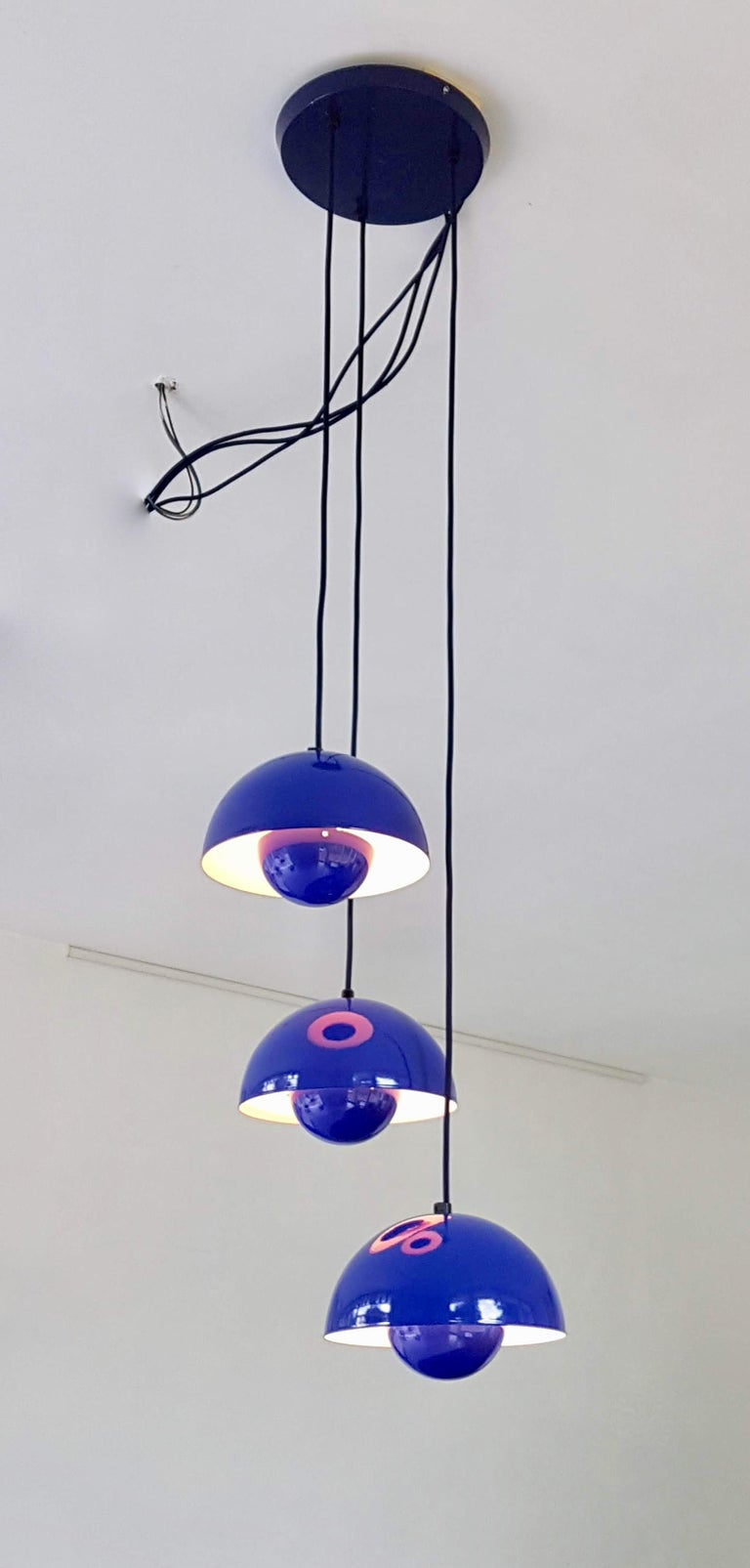 Cluster lamp by Verner Panton, Louis Poulsen Denmark consisting of three iconic 'Flower Pot' lamps mounted on a ceiling plate. The flower pot with its two enameled steel semicircular spheres facing each other is a brilliant colorful design that was
