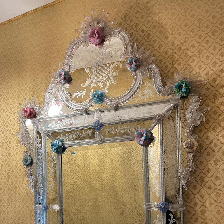 An array of leaves and frond details in antique-finished crystal embellish the sinuous frame of this sublime, one-off mirror handcrafted by Venetian master glassmakers. The three-dimensional flower inserts in multicolored glass paste add a touch of