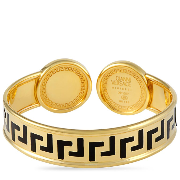 """This Versace Medusa bracelet is made out of 18K yellow gold and black enamel. It weighs 69.4 grams and boasts a 3"""" diameter. This bracelet includes the manufacturer's box."""