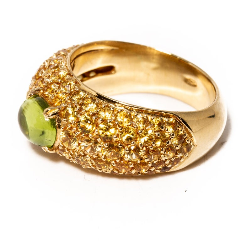18k gold half band ring by Versace. Set with yellow gemstones and cabochon peridot - 7.7mm x 5.8mm. Measures - 7, ring band is 10mm at widest point. Weight 10.2 grams. Marked Gianni Versace 750 GV.