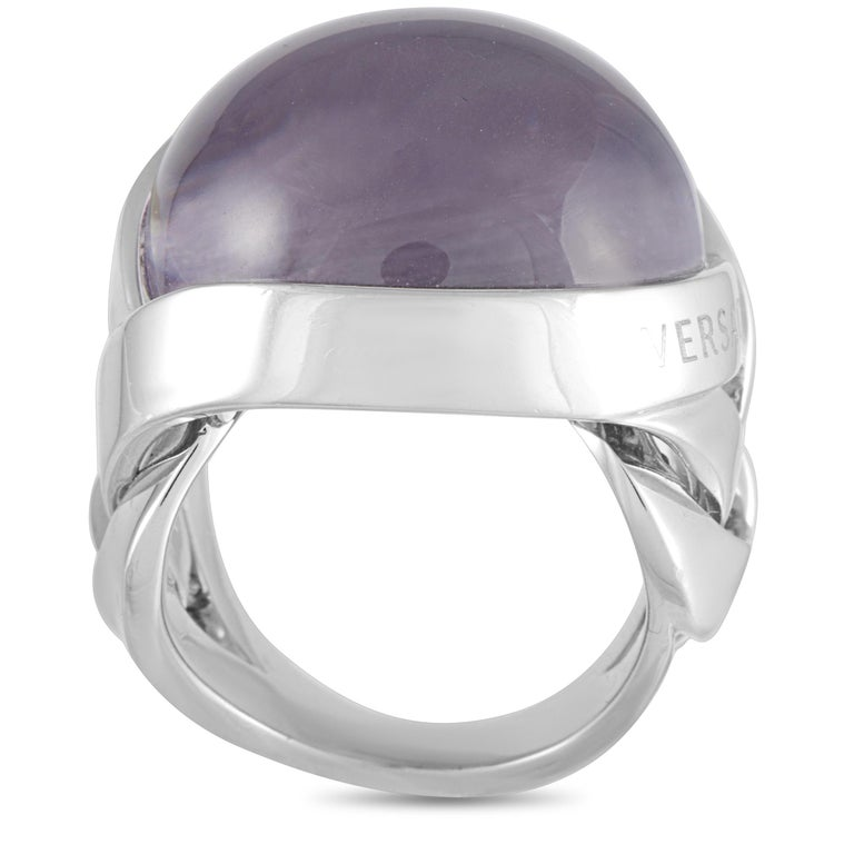 This Versace ring is crafted from 18K white gold and set with an amethyst. The ring weighs 28 grams, boasting band thickness of 17 mm and top height of 11 mm, while top dimensions measure 23 by 23 mm.    Offered in estate condition, this item