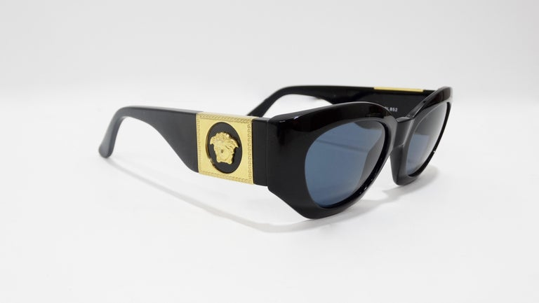 Your new everyday sunnies are here! Circa late 1980s, these Versace sunglasses feature a black frame, dark blue lenses, and a subtle cat eye shape. On both arms are gold toned Medusa heads with the signature Greek key. Signed Gianni Versace Made in