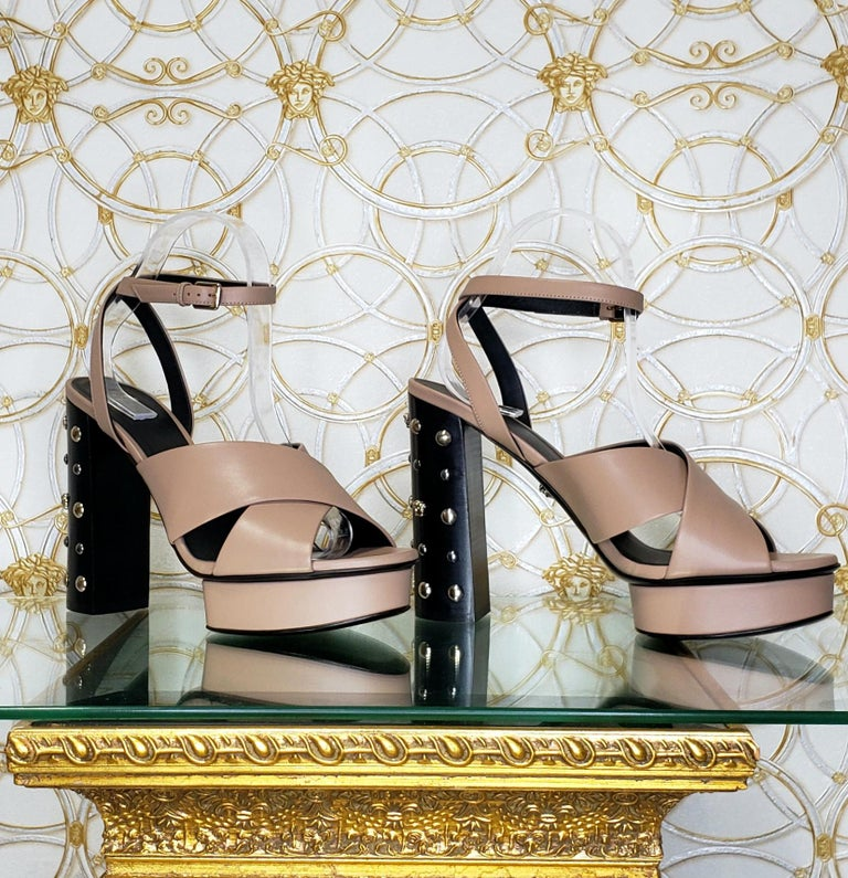 VERSACE   Beige leather sandals shoes with gold and silver studs and famous Medusa Studs  DETAILS:  Open toe and heel  Buckling ankle strap closure  Content: 100% Leather (Lining and Sole)    Color: Beige, black heel  Heel: 5 1/8 inches  Platform: 1