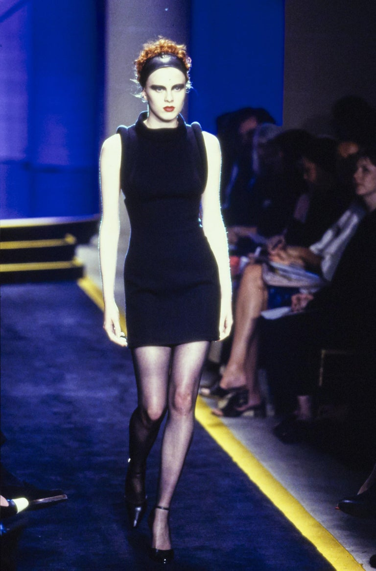 Resurrection Vintage is excited to offer a rare and unusual Atelier Versace black broadtail and leather dress from Gianni Versace's last couture collection. The dress features padded sculptural leather sleeves, square neck, mini length, full lining,