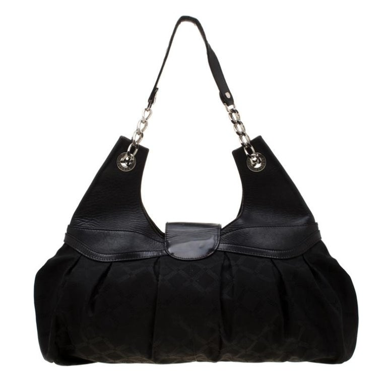 This modern handbag by Versace is all you need in your bag collection. Crafted from canvas and leather it is held by a single handle and features a fabric lined interior that is durable. Make a statement while carrying this black bag.  Includes: The