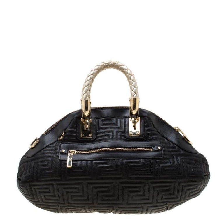 This Versace satchel carries an outstanding design and a fabulous interplay of leather and gold-tone hardware. It has a top zipper leading to a satin interior while being held by two braided handles. The quilt detailing and the brand label on the