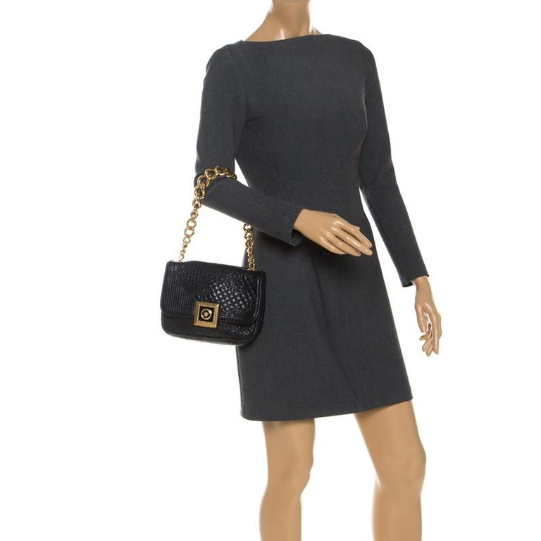 Embrace classic style with this chic bag by Versace. An example of luxe fashion, this beautifully crafted bag comes with a spacious fabric-lined interior. Made of black leather, the body features intricate quilt detailing that adds interest. It is