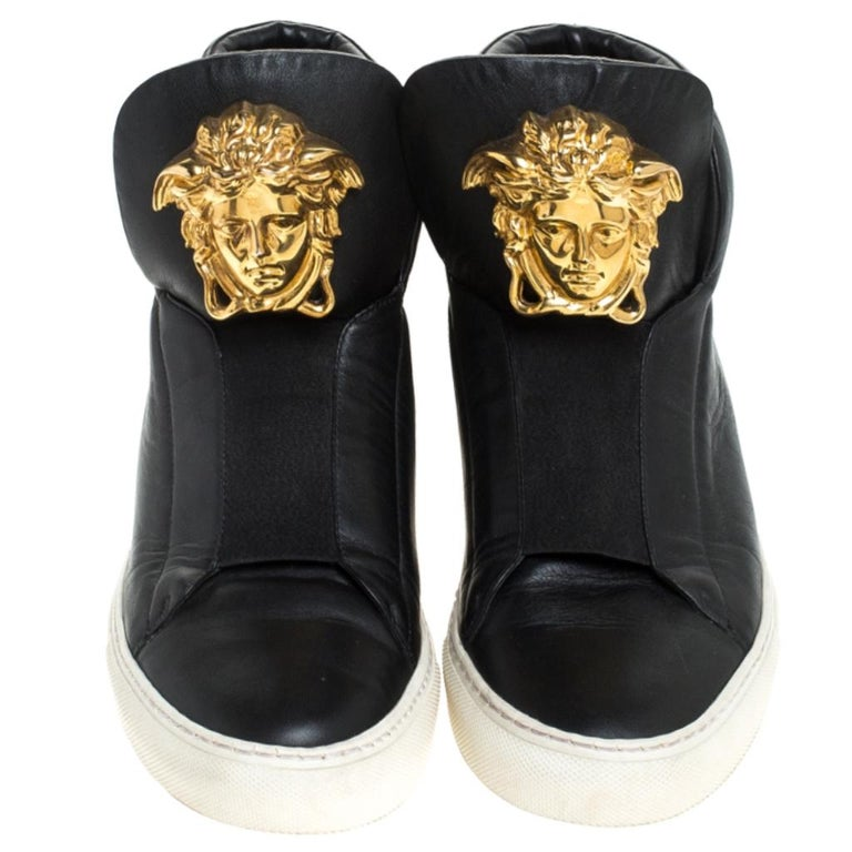 These sneakers from Versace are effortlessly suave and amazingly stylish. Brimming with fabulous details, these black sneakers are crafted from leather into a high-top silhouette and feature a gold-tone Medusa logo at the tongue. Comfortable soles