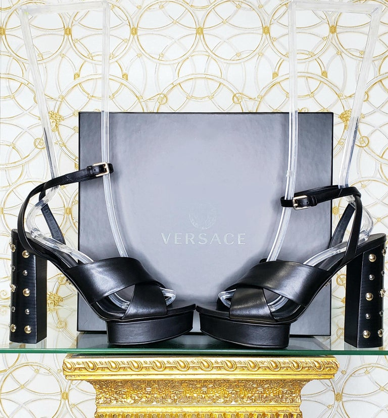 VERSACE  Black leather sandals shoes with gold and silver studs and famous Medusa Studs  DETAILS:  Open toe and heel  Buckling ankle strap closure  Content: 100% Leather (Lining and Sole)       Color: Black  Heel: 5 1/8 inches  Platform: 1 inch