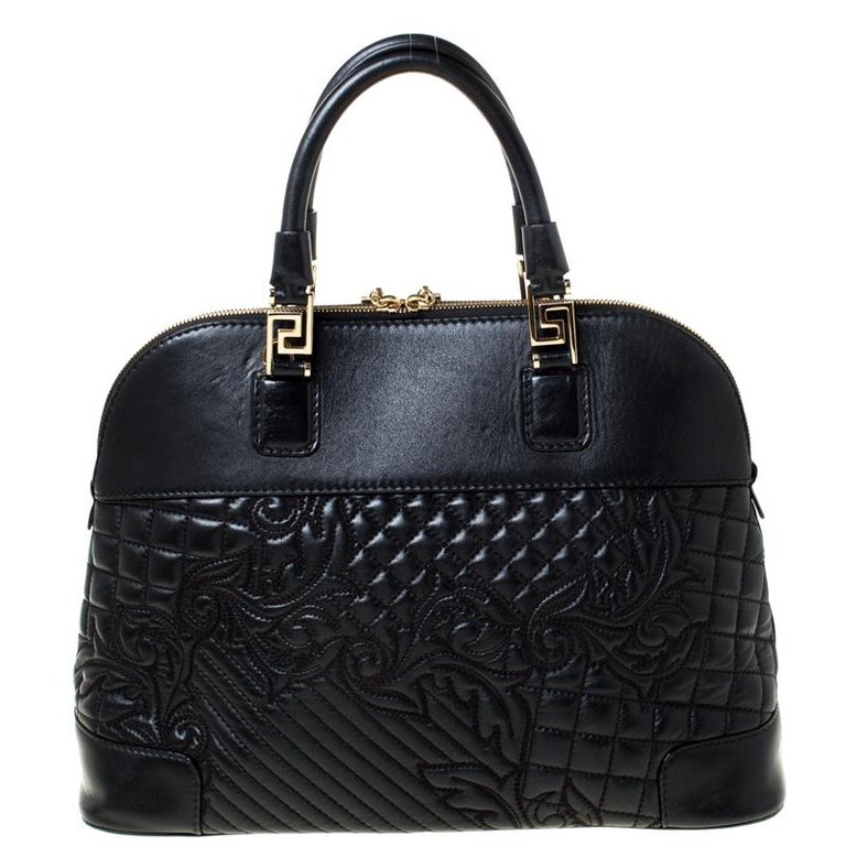 This black satchel from Versace will give you days of style and ease. It is crafted from leather and features a dangling gold-tone charm. It is equipped with a spacious fabric interior, two handles and metal feet.  This black satchel from Versace