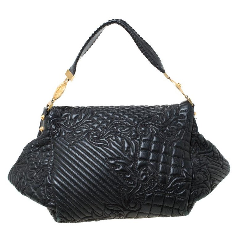 This Versace handbag is meticulously crafted from quilted leather. The Barocco bag delights not only with its appeal but structure as well. It is held by a single handle, adorned with a lovely embroidery all over and equipped with a spacious satin
