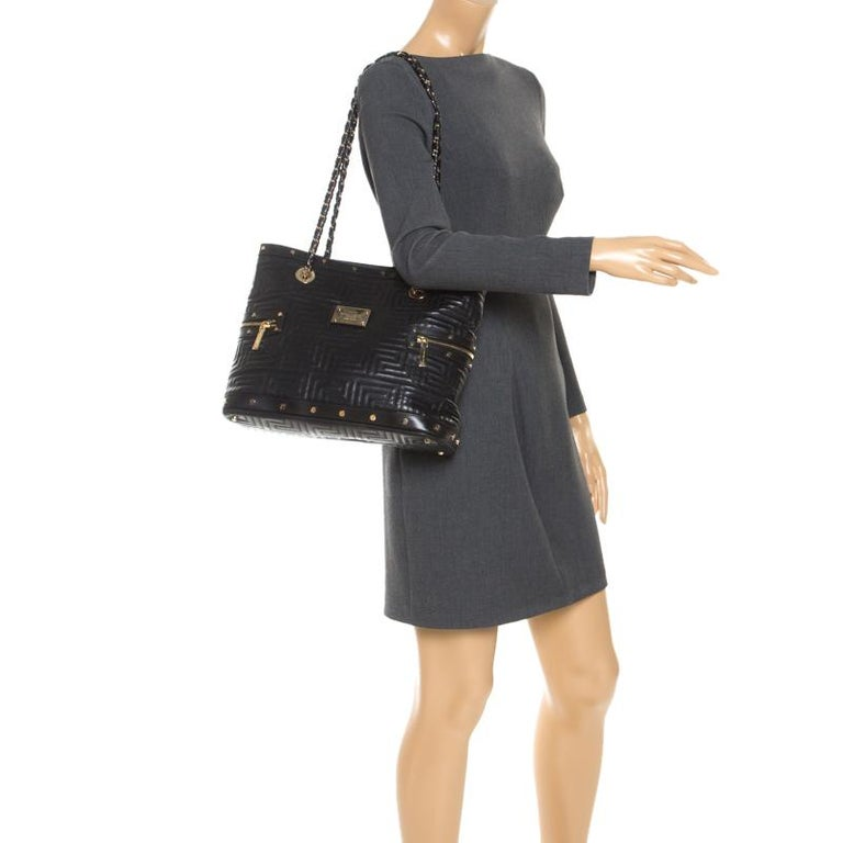 Crafted to perfection, this black Versace tote is crafted from quilted leather. It features top handles, gold-tone hardware, zipper detailing on both the sides and a metal plaque with brand's name embossed on the front. The tote opens to a