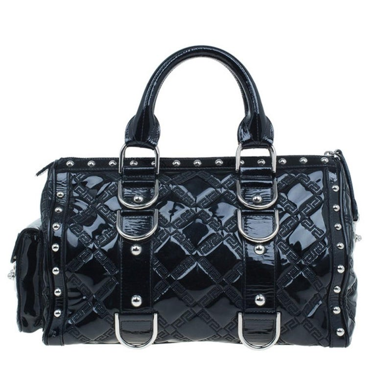 This over the top Versace 'Snap Out of It' satchel is a bold statement making bag from the fashion forward Italian label. Crafted from black quilted Versace logo patent leather, it is accented with black braided handles, a flap pocket on the left