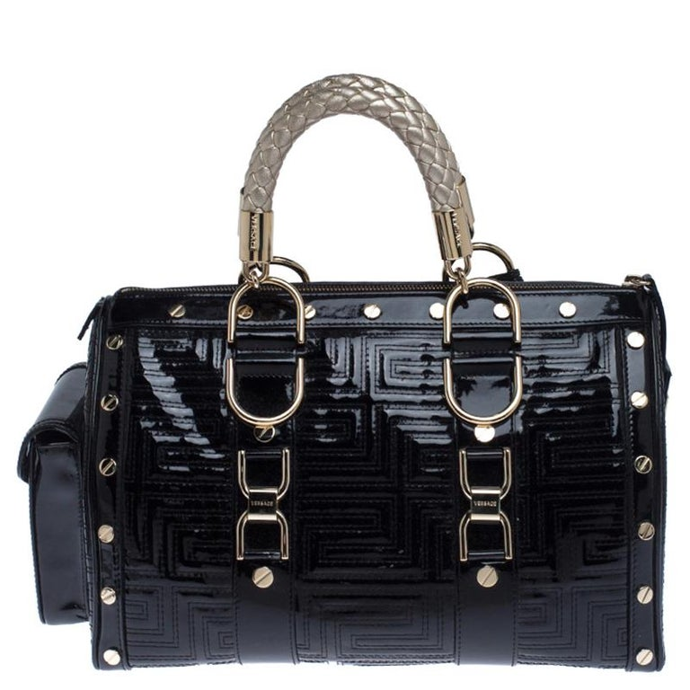 This bold and eye-catching Versace Snap Out Of it satchel is sure to make heads turn. Crafted from quilted patent leather the bag is accented with a Gianni Versace Couture plate and gold-tone studded hardware. It features dual handles and a top