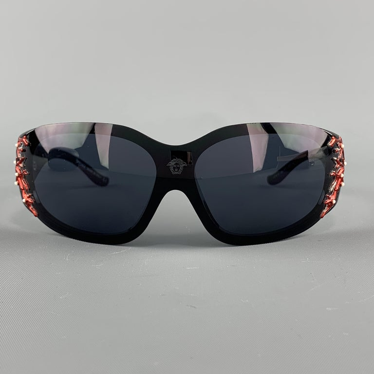 VERSACE shield sunglasses come in black acetate with a Medusa frontal decal  and arms with metallic red coral reef motif. Minor wear. With case. Made in Italy.  Very Good Pre-Owned Condition.  Measurements:  Length: 15 cm. Height: 5 cm.