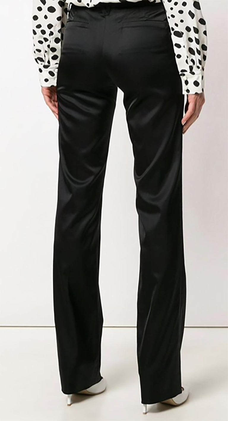 Versace black bootcut satin trousers featuring a low rise, a waistband with belt loops, a concealed front fastening, front welt pockets, rear welt pockets, a slim fit and a regular length.  In excellent condition. Made in Italy.  Estimated size