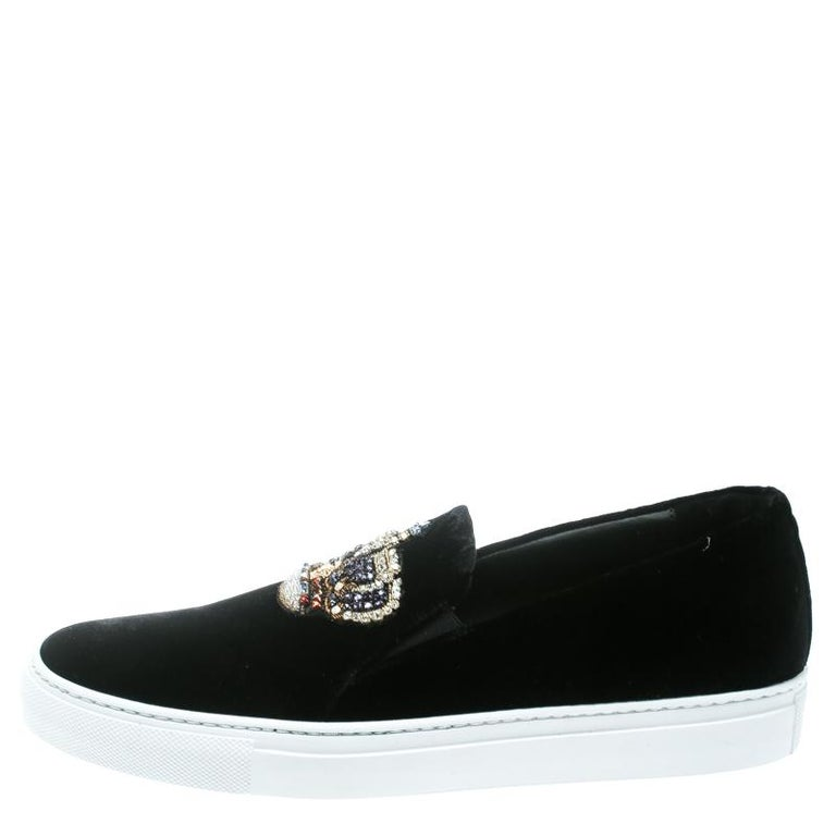 Lend the luxury appeal to your casuals with these Corona sneakers from Versace. Crafted from black velvet, they are detailed with crystal embellished crown motif on the vamps and rubber soles with an easy slip-on silhouette. They are the perfect