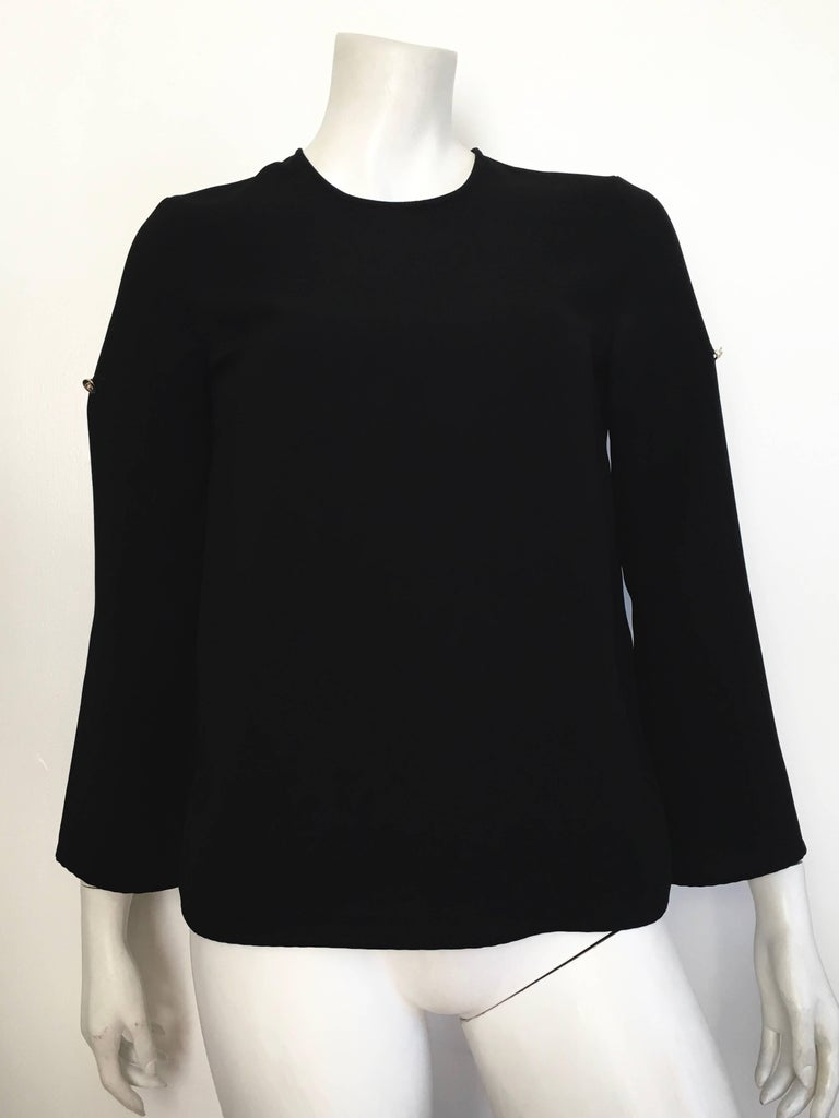 Versace black wool long roll up tabs sleeves is labeled an Italian size 38 and fits a size 4. There are 3 small gold Versace Medusa buttons on this blouse; one button on each of the sleeves that you can roll up and one button on the peek a boo back