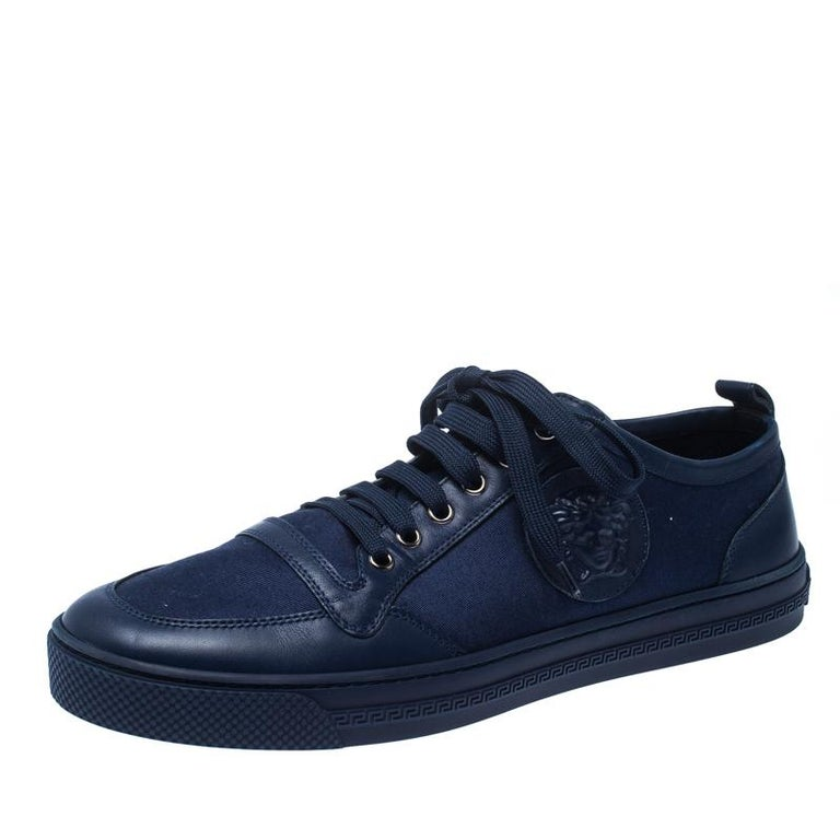 A pair of finely crafted canvas and leather sneakers from Versace to bring out the chic style in you. Let your fashion choice speak for you as you wear these trendy blue sneakers. They come with lace-up on the vamps and rubber soles.  Includes: