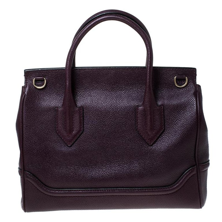This Palazzo Empire bag from Versace is a fabulous piece. The bag comes in a luxurious burgundy exterior in leather and designed with their signature Medusa motif on the flap that reveals a spacious fabric interior. It features dual top handles and